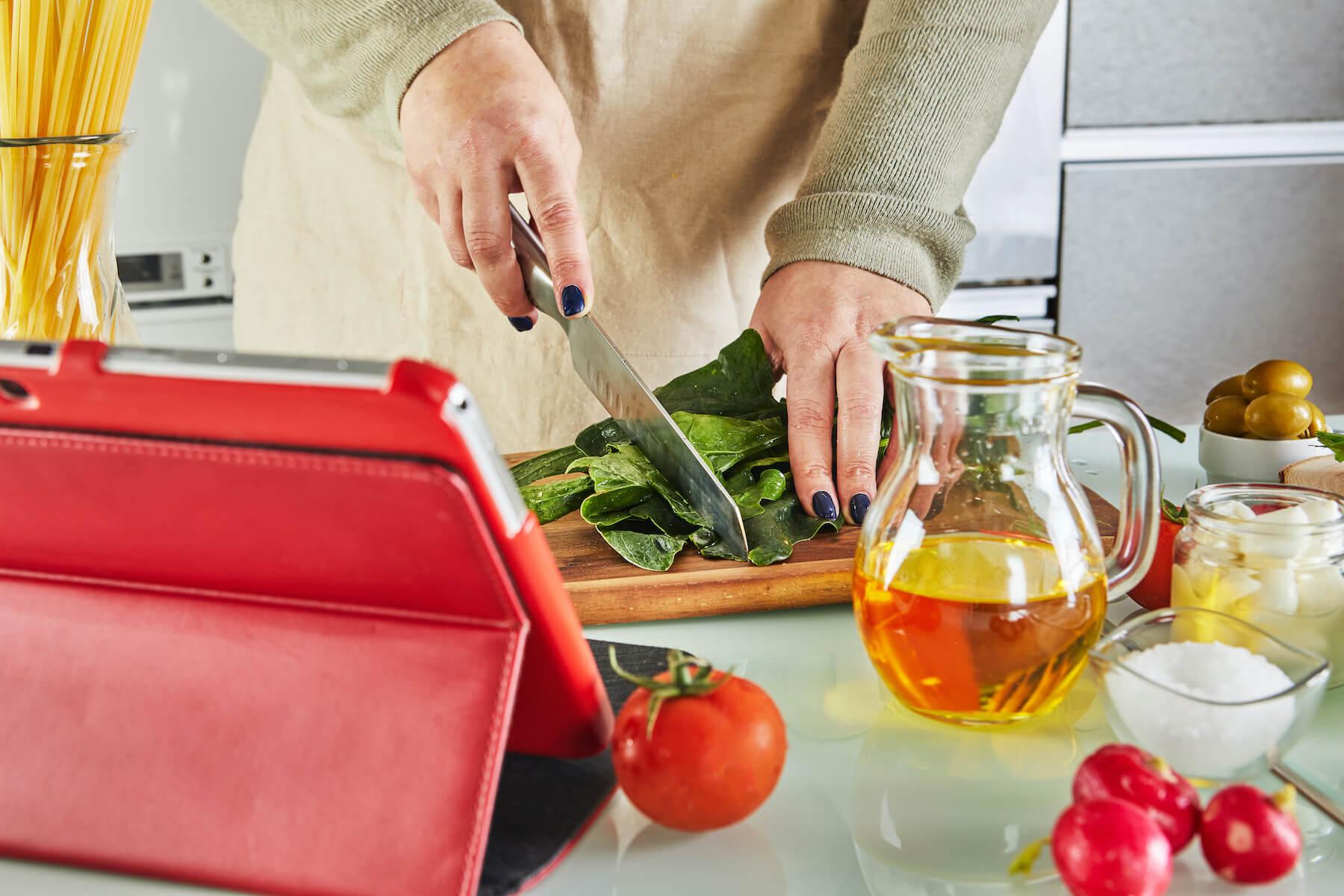 Frau schneidet Gemüse vor Tablet