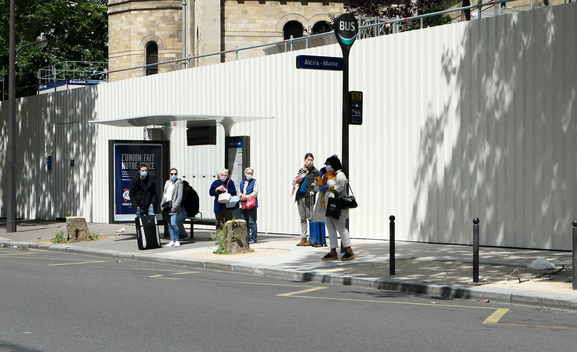 Maskierte Menschen warten in Paris auf den Bus.