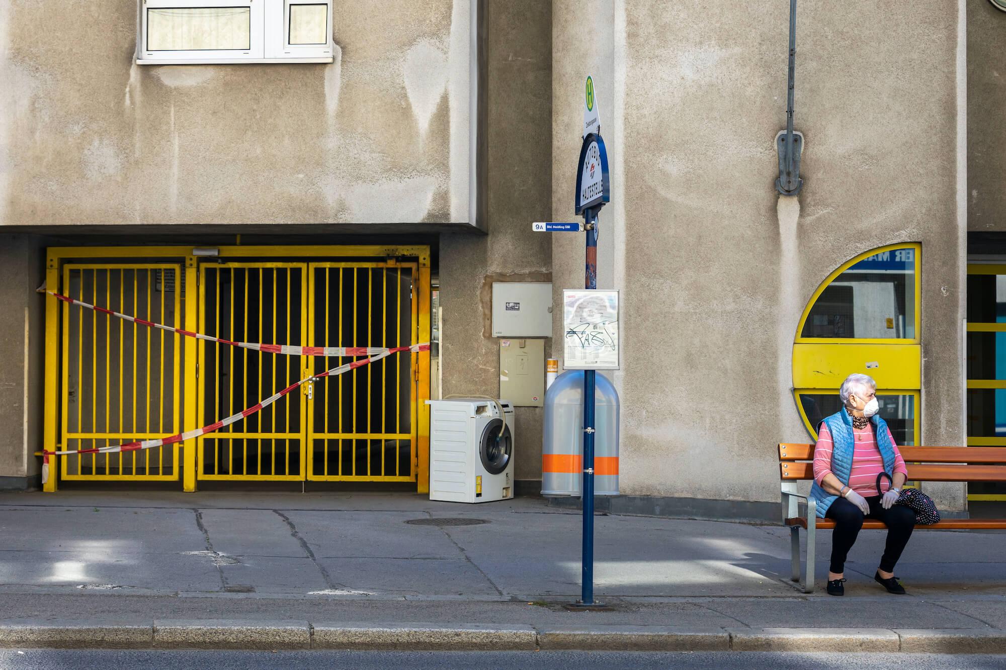 Frau trägt Maske und wartet in Wien auf ihren Bus.