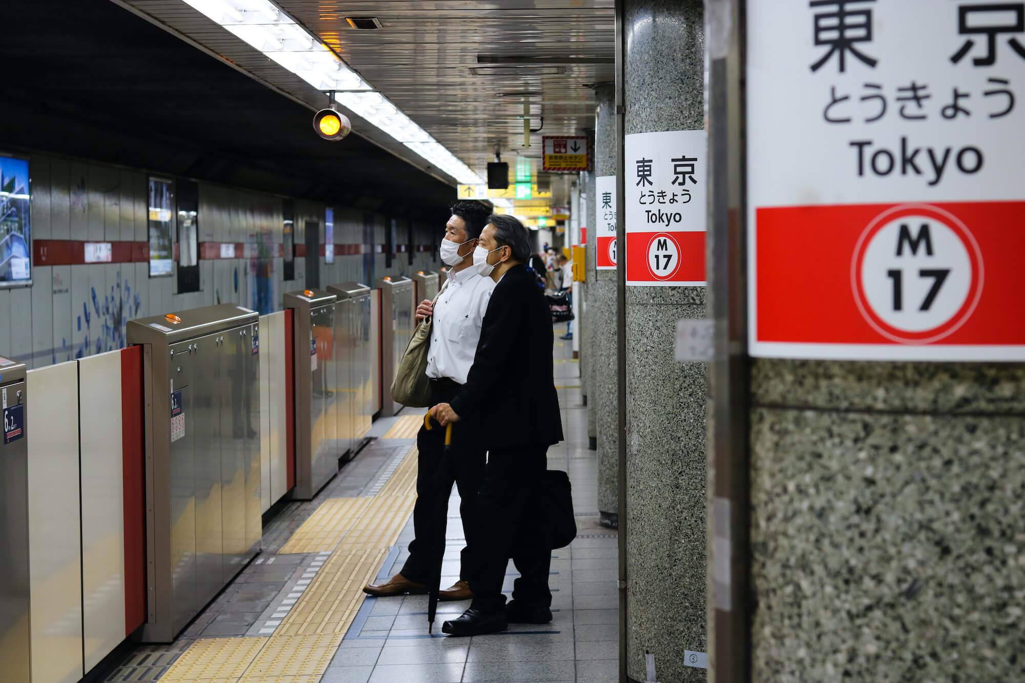Maskierte Männer warten in Tokio auf ihre Bahn.