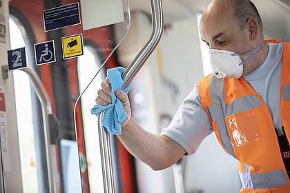 DB Mitarbeiter reinigt Haltestange.