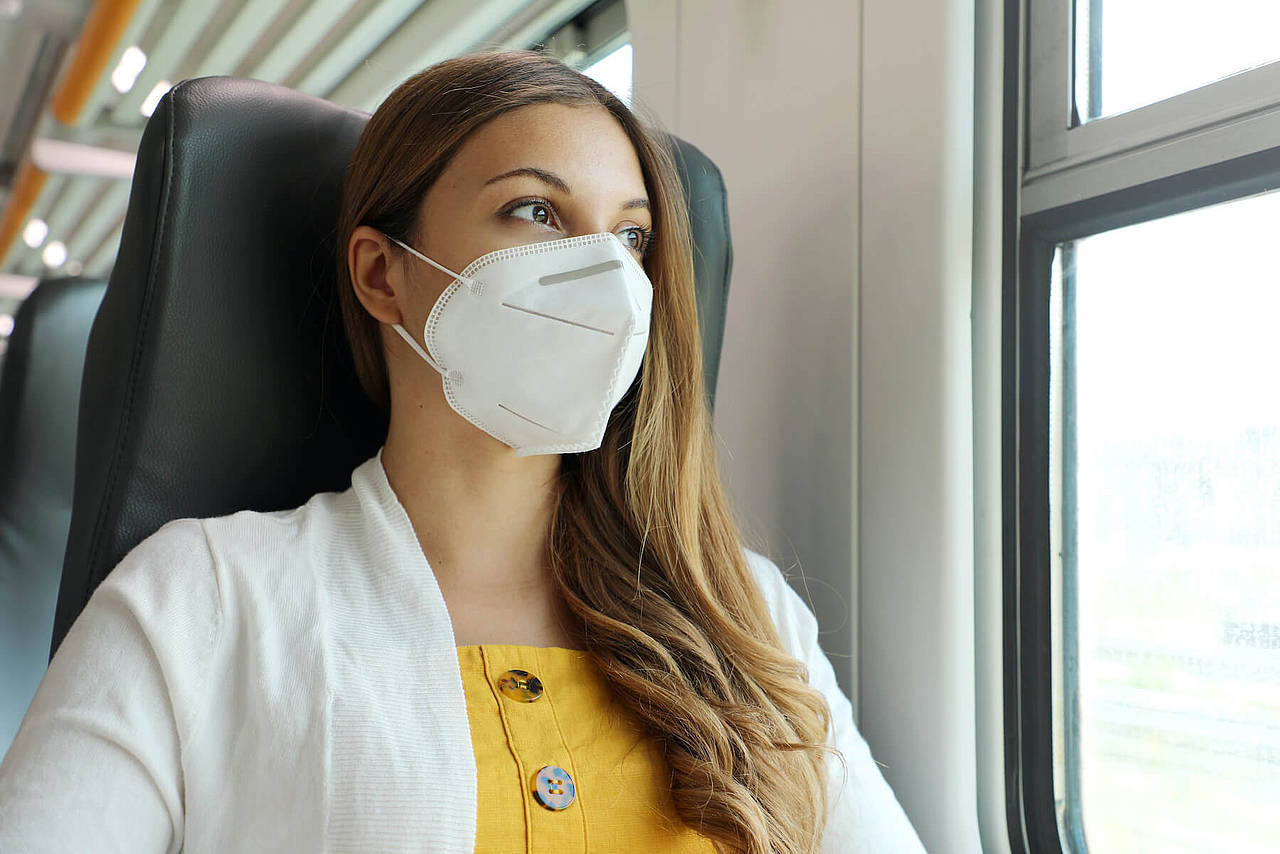 Frau trägt FFP2-Maske in der Bahn