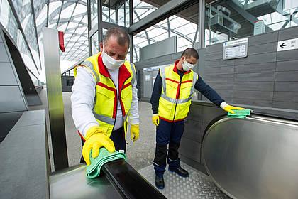 Mitarbeiter des Hochbahn-Hygieneteams reinigen Handläufe.