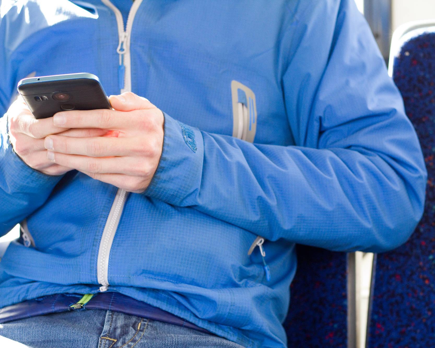 Mann mit Smartphone im Bus