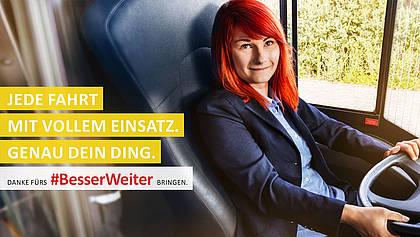 Busfahrerin lächelt am Steuer.