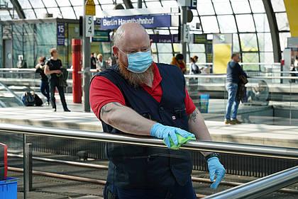 DB Mitarbeiter reinigt Handlauf im Bahnhof.