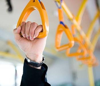 Fahrgast hält sich an Halteschlaufe in Bus fest