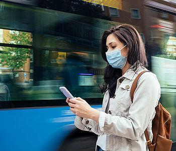 Frau steht mit medizinischer Maske vor einem Bus