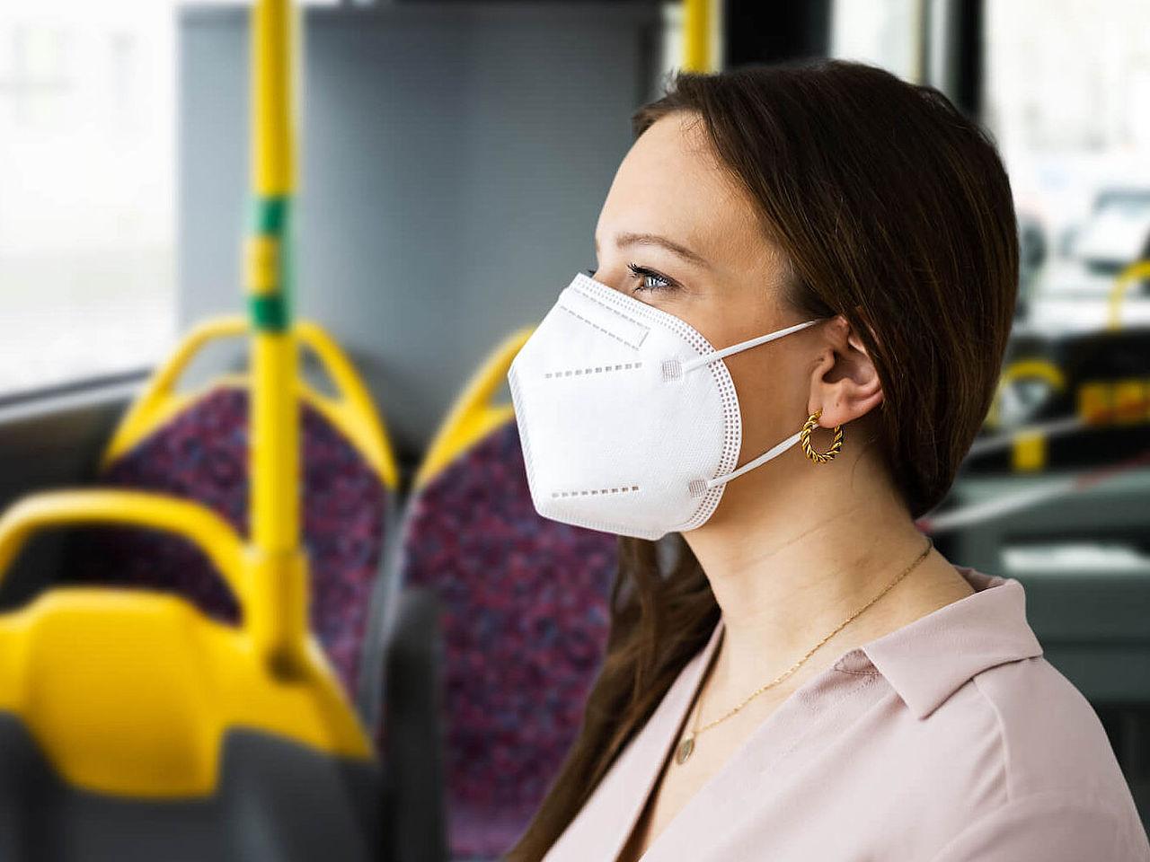 Frau steht im Bus und trägt eine FFP2-Maske