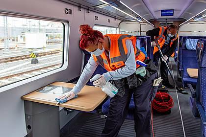 DB Mitarbeiterin reinigt Fahrzeuginnenraum.
