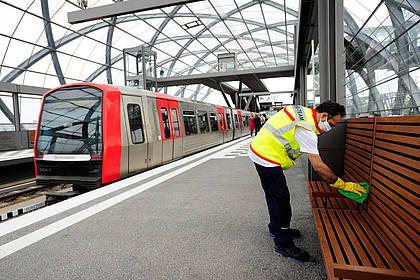 Mitarbeiter des Hochbahn-Hygieneteams reinigt Sitzfläche am Bahnsteg.