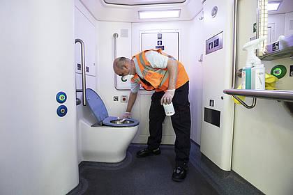DB Mitarbeiter reinigt Zugtoilette.