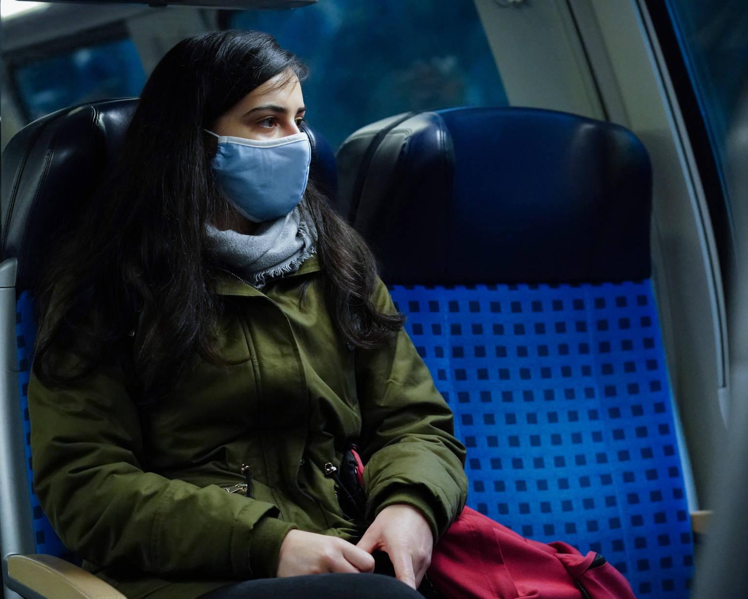 Frau trägt Gesichtsmaske und fährt Bahn
