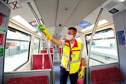 Mitarbeiter des Hochbahn-Hygieneteams reinigt Bahn-Innenraum.