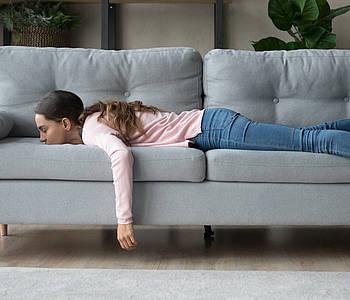 Frau liegt erschöpft auf dem Sofa