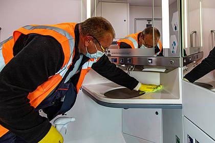 DB Mitarbeiter reinigt Waschbecken auf Bordtoilette.