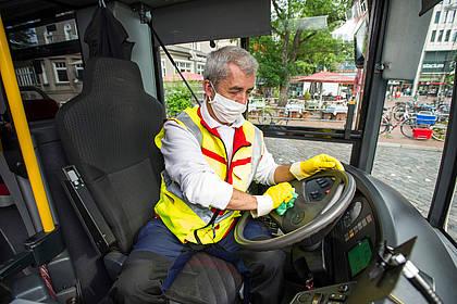 Mitarbeiter des Hochbahn-Hygieneteams reinigt das Bussteuer.