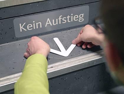 Ein Pfeil wird auf einer Stufe des DB-regios angebracht.