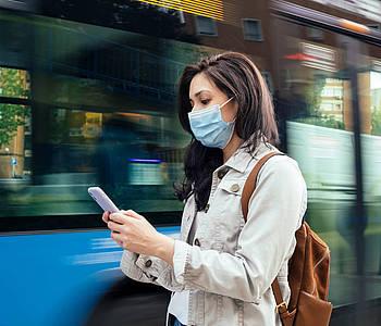 Frau mit Maske steht vor einem Bus und schaut auf ihr Smartphone