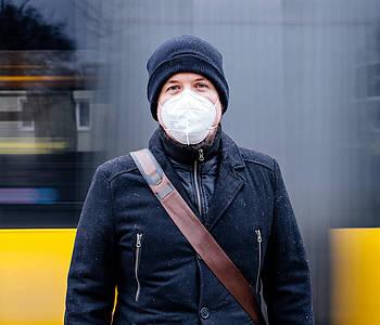 Mann mit FFP2-Maske steht vor einem fahrenden Bus