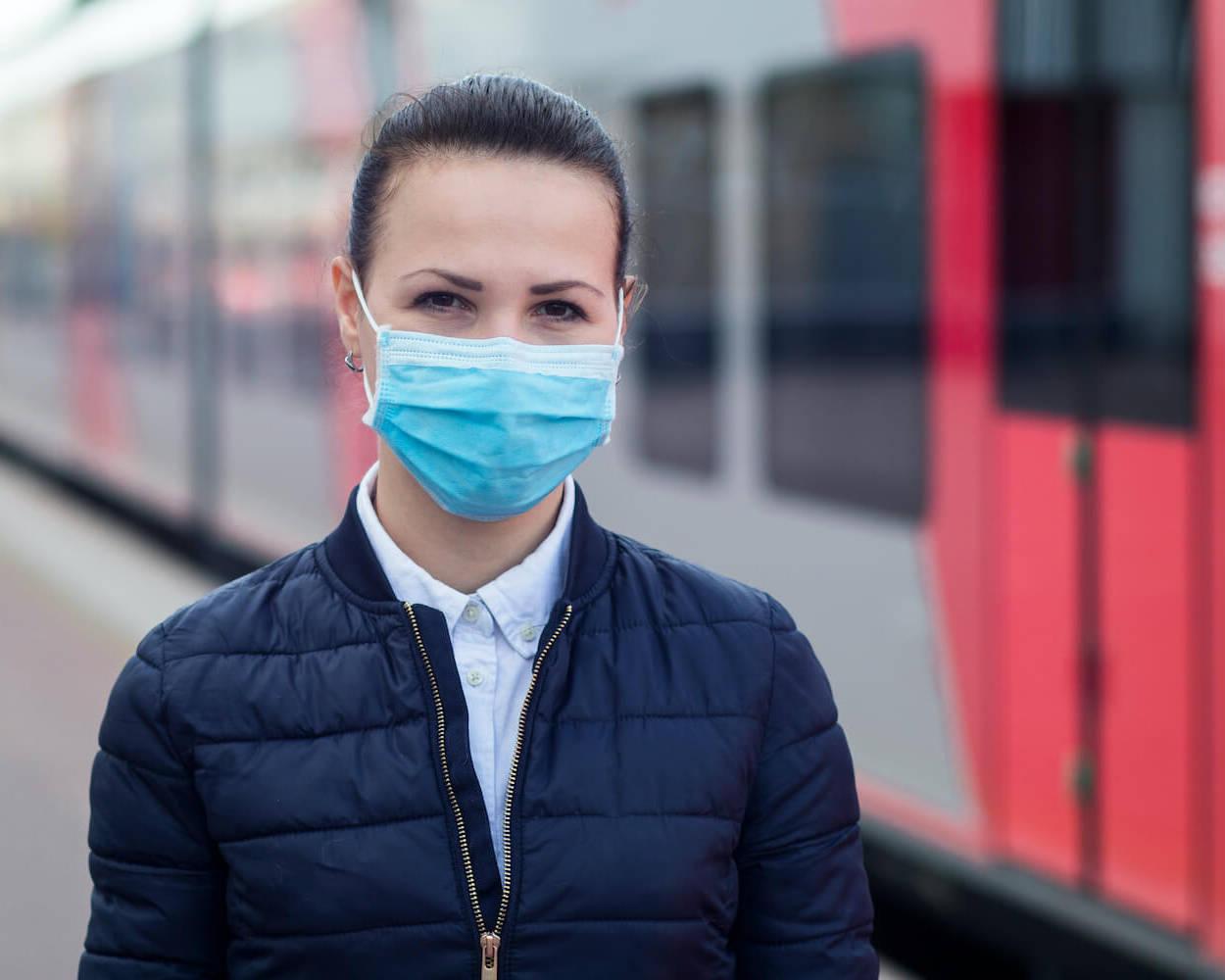 Eine Frau mit medizinischer Maske steht am Gleis vor einer Bahn