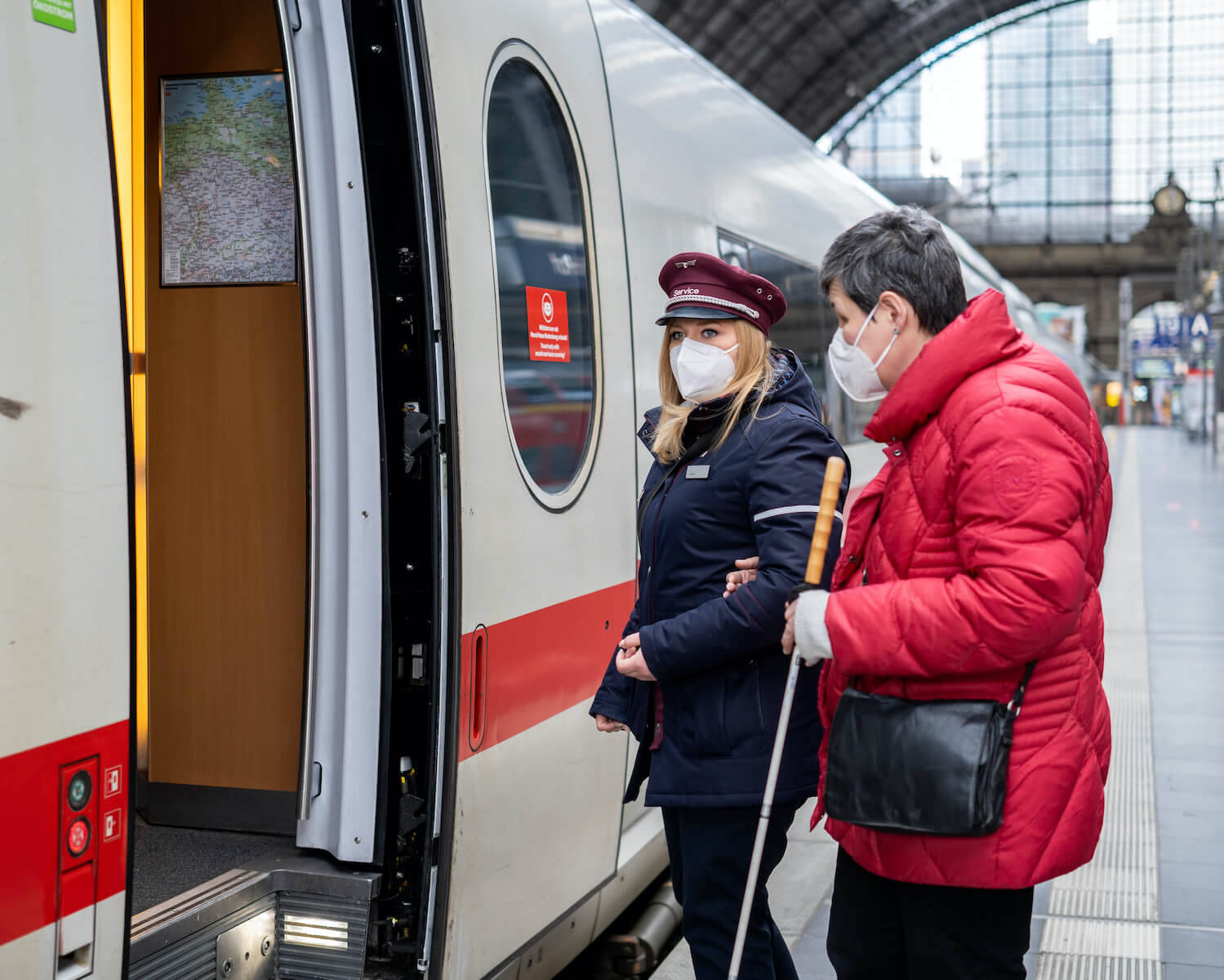 Eine DB-Mitarbeiterin mit FFP2-Maske begleitet eine Frau mit eingeschränkter Sehfähigkeit in einen ICE