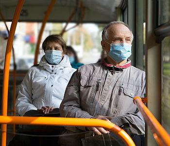 Menschen sitzen mit medizinischer Maske im Bus