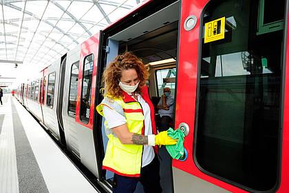 Mitarbeiterin des Hochbahn-Hygieneteams reinigt Druckknöpfe einer Bahn.