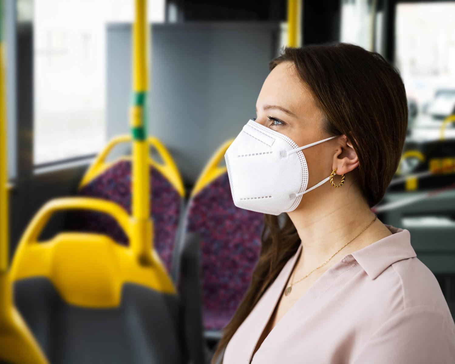 Frau mit FFP2-Maske steht im Bus