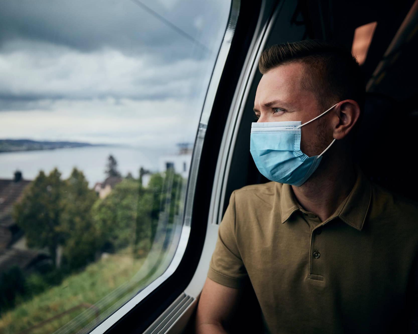 Mann sitzt mit Maske im Zug und schaut aus dem Fenster.