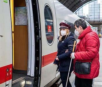 DB-Mitarbeiterin hilft einer Kundin beim Einstieg in einen ICE