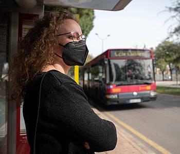 Frau mit FFP2-Maske steht an einer Bus-Haltestelle