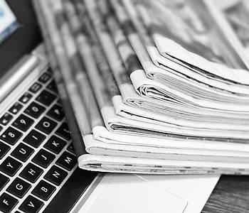 Zeitungen liegen auf einem Laptop