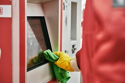 DB Mitarbeiter reinigt Fahrkartenautomaten.