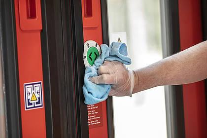 DB Mitarbeiter reinigt Türöffner.