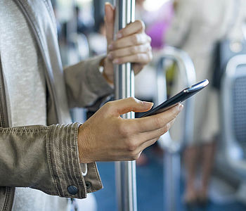 Eine Frau fährt Bus und schaut dabei auf ihr Smartphone