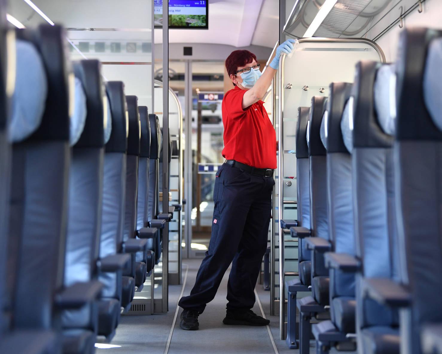 DB Mitarbeiterin reinigt Zuginnenraum.