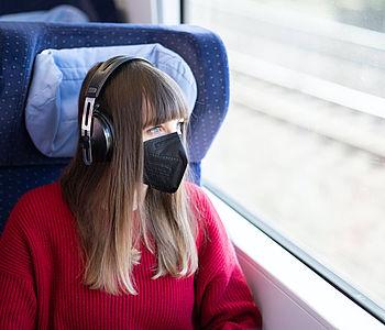 Frau sitzt mit Maske in der Bahn und hört Musik