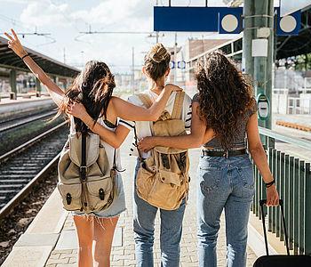 Eine Gruppe von Mädchen stehen mit Koffer am Bahngleis